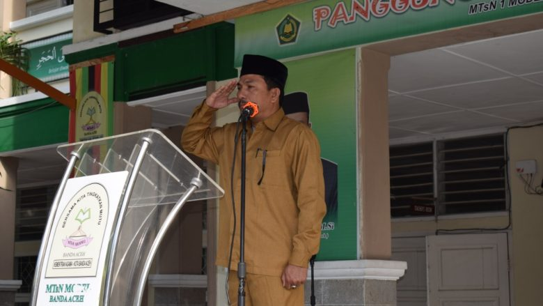 PENGHORMATAN: Kasi SarPras Pendidikan Madrasah (Penmad) Kanwil Kemenag Aceh, Syafruddin, S.Ag saat memberikan penghormatan pemimpin upacara. Senin,(14/10/2019)
